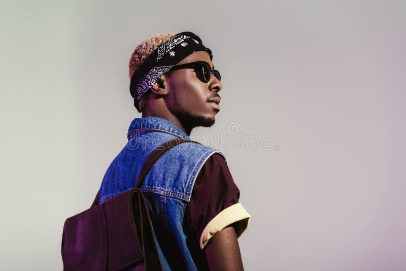 opinião traseira o homem afro-americano novo à moda nos óculos de sol e na trouxa de couro que olham afastado imagem de stock