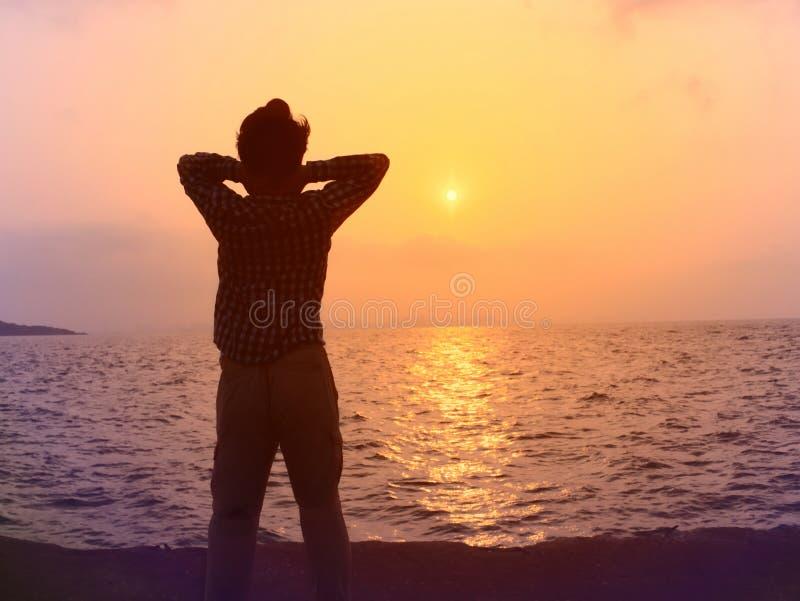 Opinião traseira o homem asiático novo relaxado que está com fundo do por do sol imagens de stock royalty free