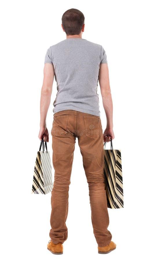 Opinião traseira o homem considerável com sacos de compras fotografia de stock
