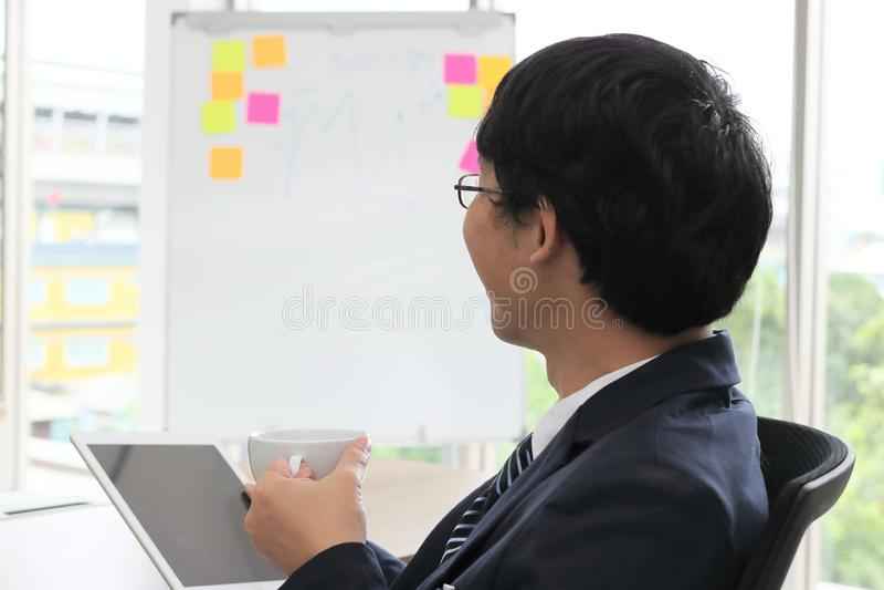 Opinião traseira o homem de negócio asiático novo que guarda o copo de café e que olha a tabuleta nas mãos no escritório imagem de stock