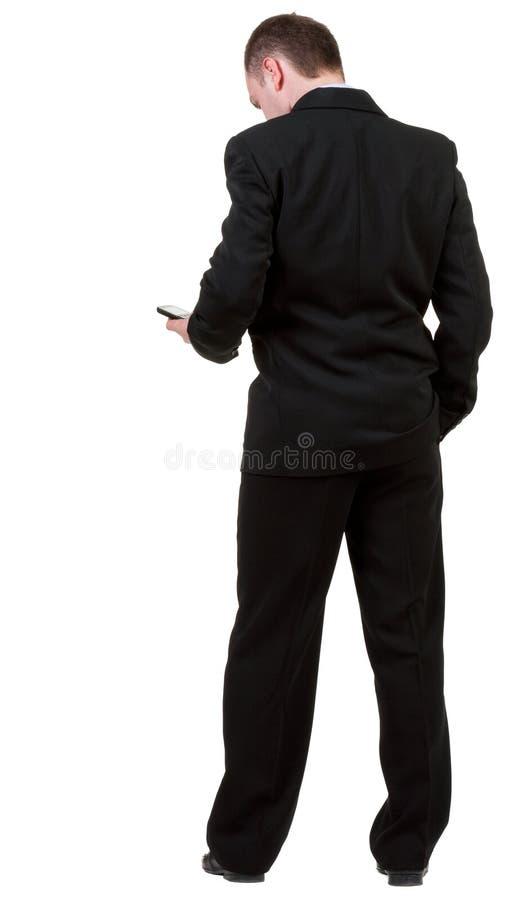 Opinião traseira o homem de negócio no terno preto que fala no phon móvel foto de stock