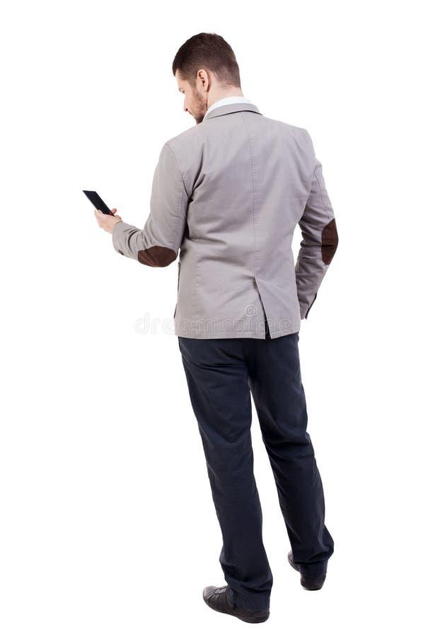Opinião traseira o homem de negócio no terno que fala no telefone celular fotos de stock royalty free