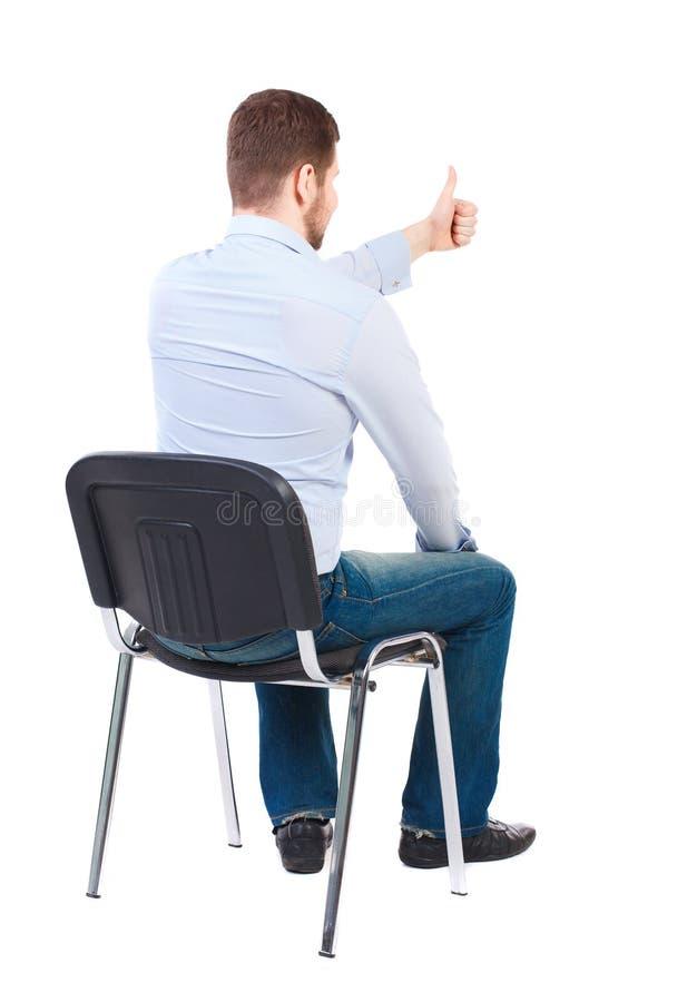 Opinião traseira o homem de negócio novo que senta-se na cadeira e nos polegares acima imagem de stock