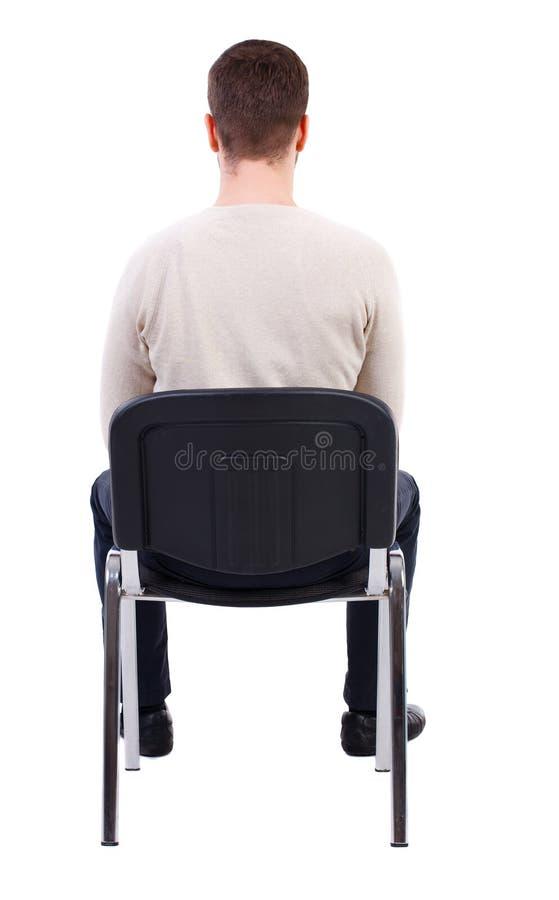 Opinião traseira o homem de negócio que senta-se na cadeira fotografia de stock royalty free