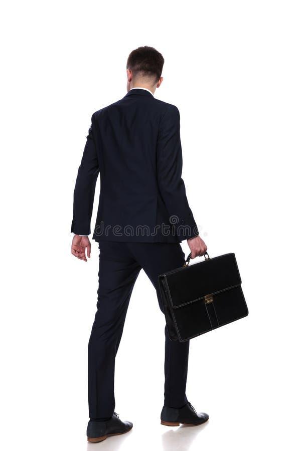 Opinião traseira o homem de negócios com passeio da mala de viagem imagem de stock