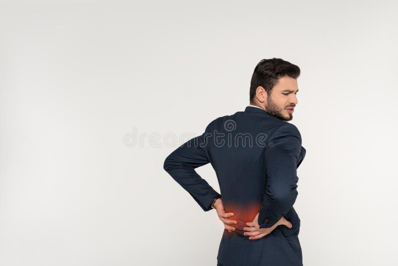 opinião traseira o homem de negócios novo que sofre da dor lombar fotos de stock royalty free