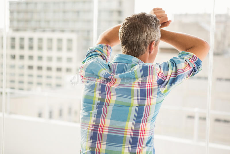 Opinião traseira o homem de negócios ocasional incomodado que inclina-se contra a janela imagem de stock royalty free