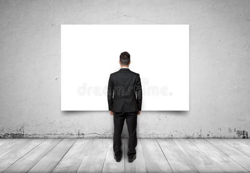 Opinião traseira o homem de negócios que olha a lona vazia branca no muro de cimento fotos de stock