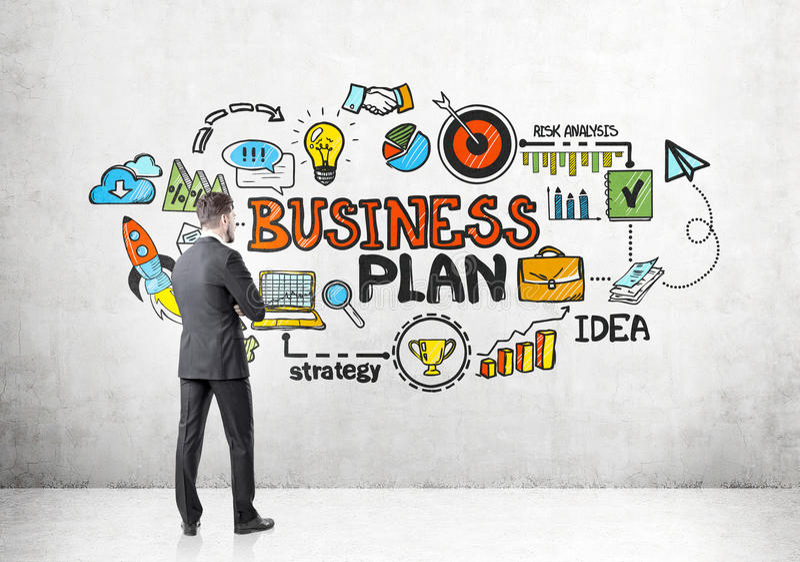 Opinião traseira o homem de negócios que olha o plano de negócios fotografia de stock