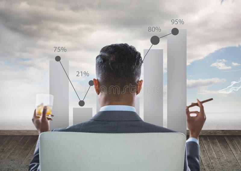 Opinião traseira o homem de negócios que senta-se na cadeira com vidro do gráfico de exame do álcool ao fumar o charuto imagens de stock