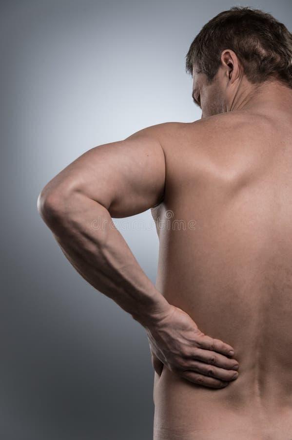 Opinião traseira o homem descamisado novo com dor nas costas imagens de stock