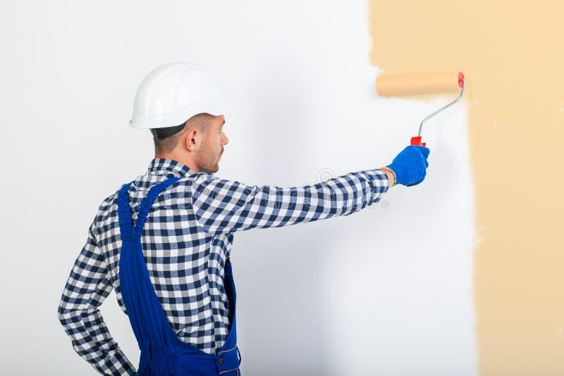 Opinião traseira o homem do pintor que pinta a parede imagens de stock