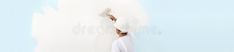 Opinião traseira o homem do pintor que pinta a parede, com rolo de pintura, i fotografia de stock royalty free