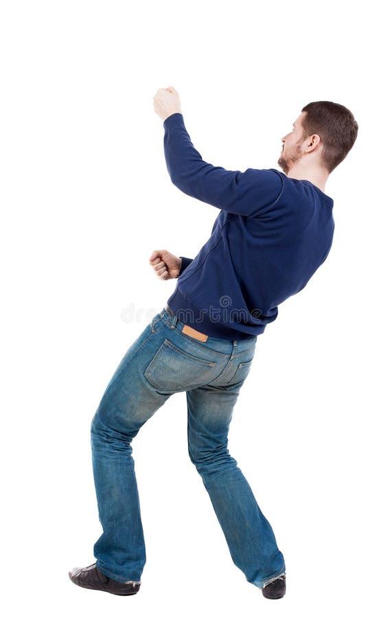 A opinião traseira o homem ereto que puxa uma corda da parte superior ou adere-se t foto de stock