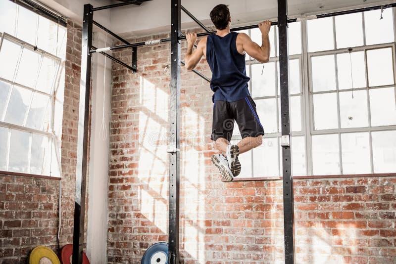 A opinião traseira o homem muscular que faz a tração levanta foto de stock royalty free