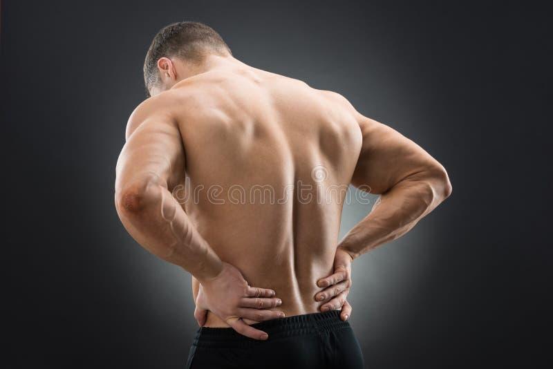 Opinião traseira o homem muscular que sofre da dor lombar foto de stock royalty free