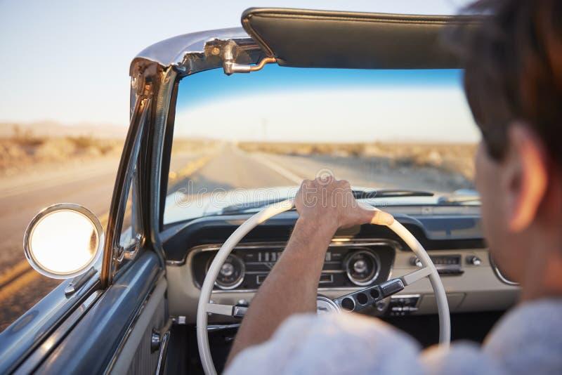 Opinião traseira o homem na viagem por estrada que conduz o carro convertível clássico para o por do sol imagem de stock royalty free