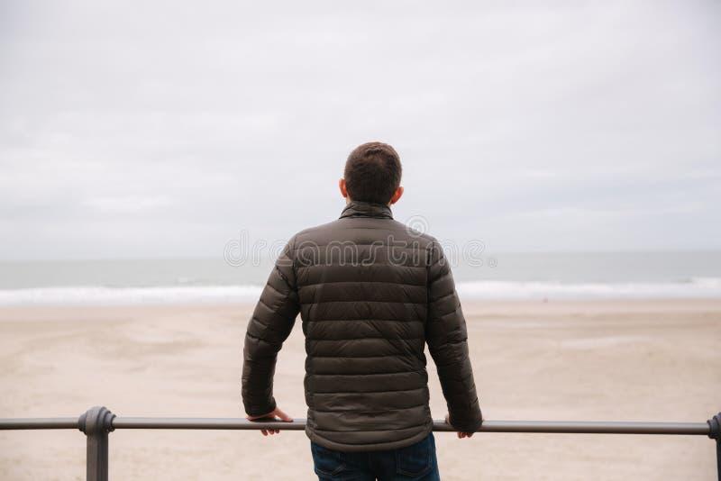 Opinião traseira o homem no revestimento caqui que olha no Mar do Norte fotos de stock royalty free