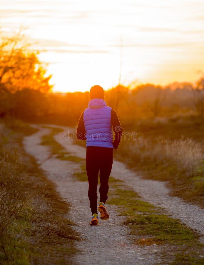 Opinião traseira o homem novo do esporte que corre fora fora da trilha da fuga da estrada para o sol do outono no por do sol com  imagens de stock