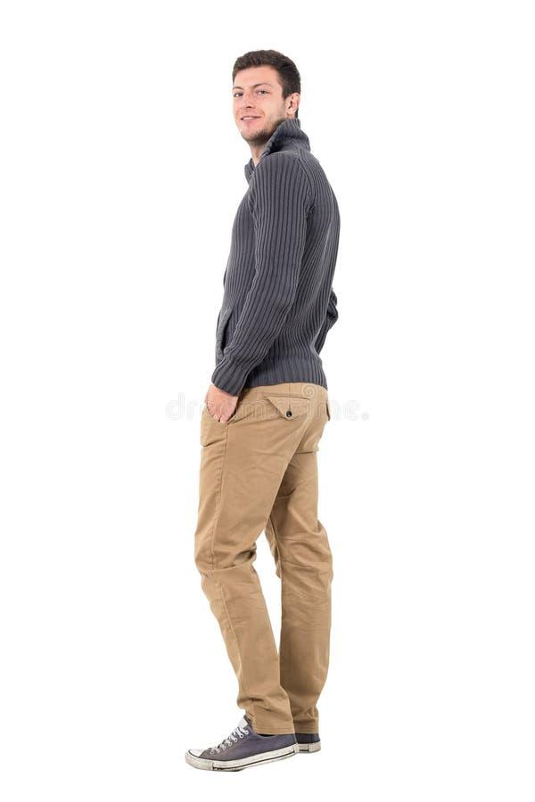 Opinião traseira o homem novo na ligação em ponte com mãos em uns bolsos que sorri na câmera imagens de stock