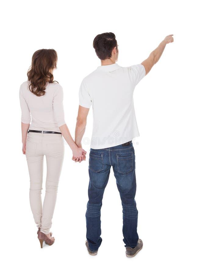 Opinião traseira o homem que aponta ao guardar a mão da mulher fotos de stock royalty free
