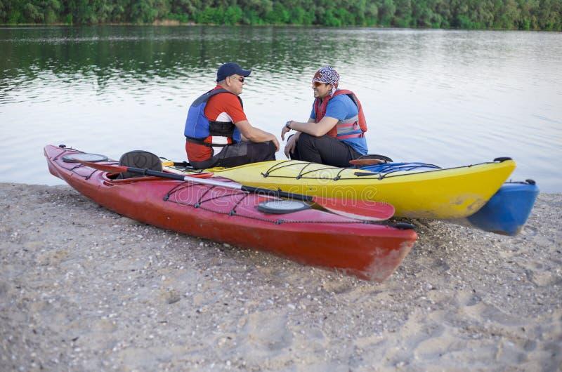 Opinião traseira o homem que rema o caiaque no lago com a mulher no fundo Acople kayaking no lago em um dia ensolarado imagem de stock royalty free