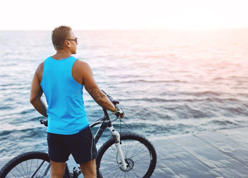 Opinião traseira o homem 'sexy' atlético com bicicleta fora no beira-mar e olhando o por do sol imagem de stock royalty free