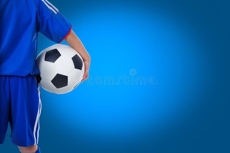 Opinião traseira o jogador de futebol da juventude no uniforme azul imagem de stock royalty free