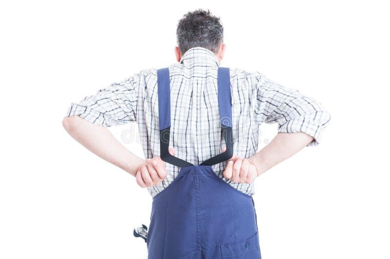 Opinião traseira o mecânico que veste macacões azuis para a proteção do trabalho imagem de stock royalty free