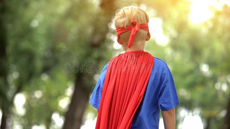 Opinião traseira o menino no traje do superman, criança sonhadora, atividade recreacional fotos de stock royalty free