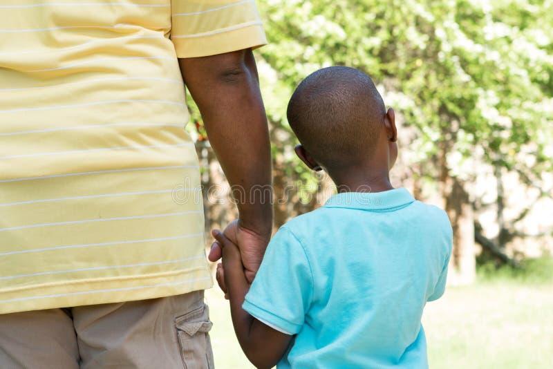 Opinião traseira o pai e o filho que guardam as mãos fotografia de stock royalty free