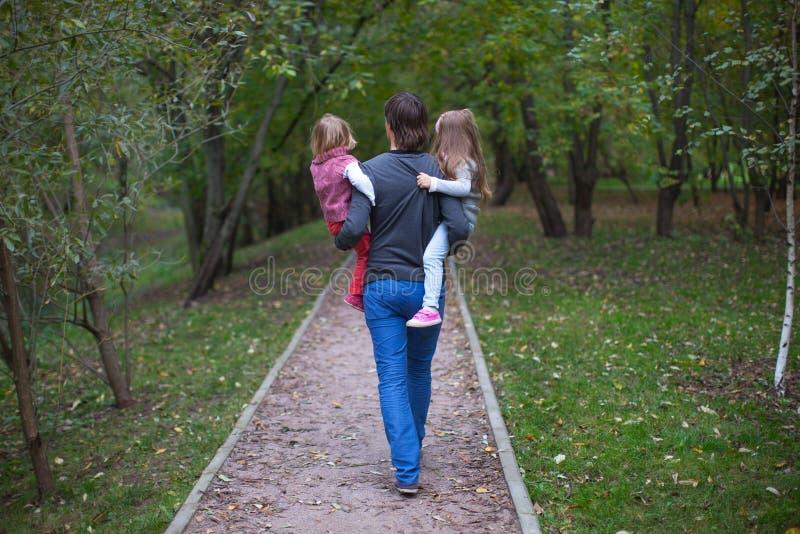 Opinião traseira o pai e suas duas filhas pequenas imagens de stock royalty free