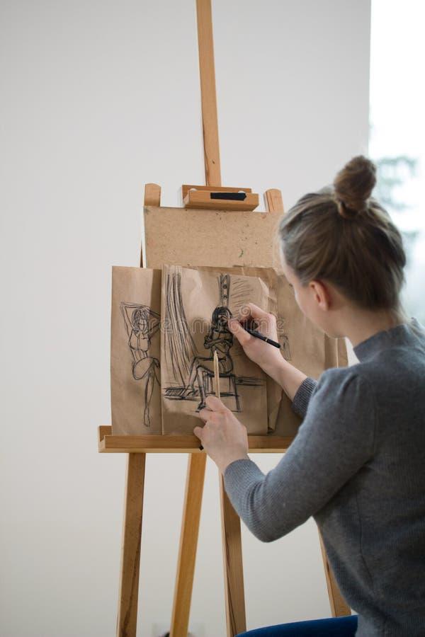A opinião traseira o pintor fêmea tira na figura do ser humano da armação foto de stock royalty free