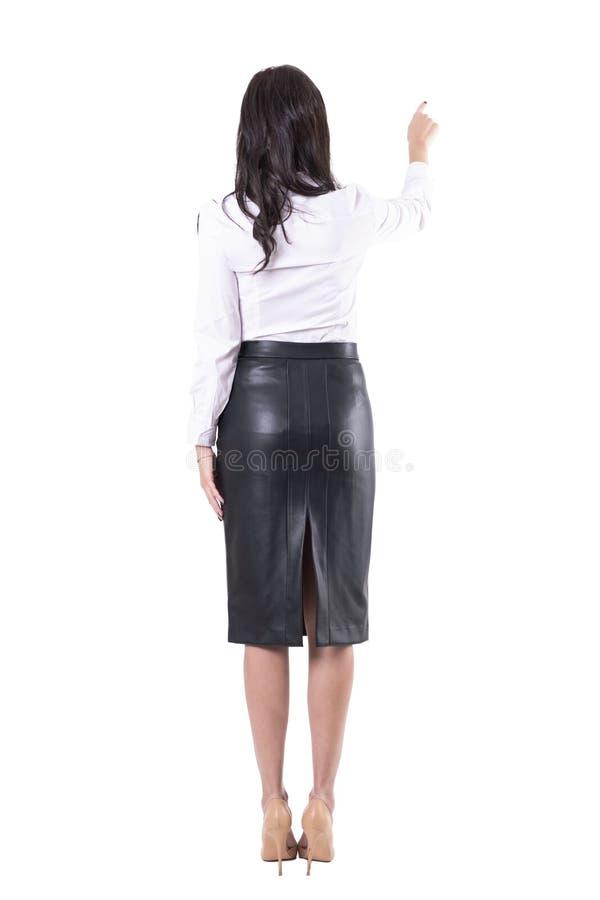 Opini?o traseira o professor da jovem mulher ou a mulher de neg?cio que apontam o dedo que mostra o espa?o vazio da c?pia foto de stock