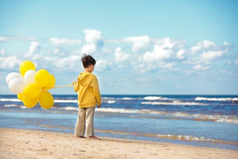 Opinião traseira o rapaz pequeno com ballons na praia imagem de stock