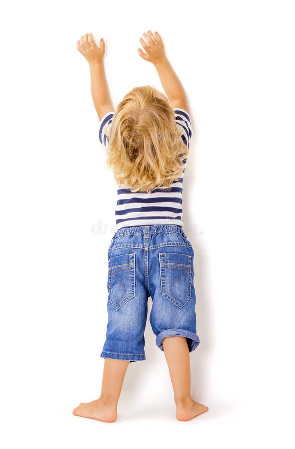 Opinião traseira o rapaz pequeno com mãos acima foto de stock