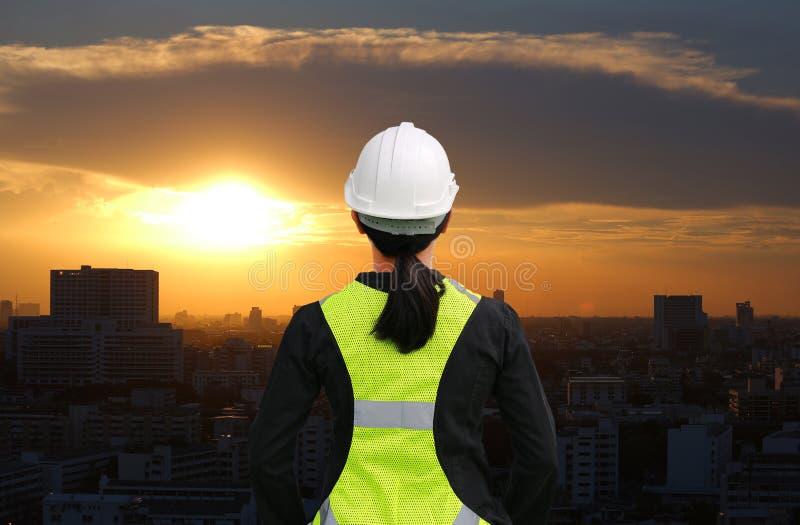 Opini?o traseira o trabalhador da constru??o f?mea contra a constru??o no por do sol no fundo da cidade de Banguecoque imagens de stock royalty free