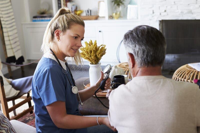 Opinião traseira o trabalhador fêmea dos cuidados médicos que mede a pressão sanguínea do homem superior durante uma visita da ca imagens de stock royalty free