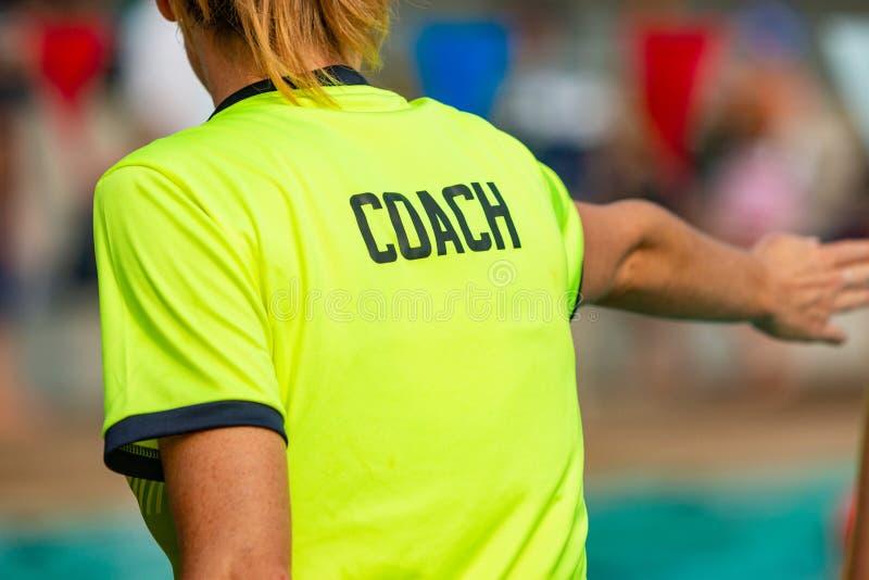 Opinião traseira o treinador fêmea da nadada que dá a instrução a seu nadador fotos de stock royalty free