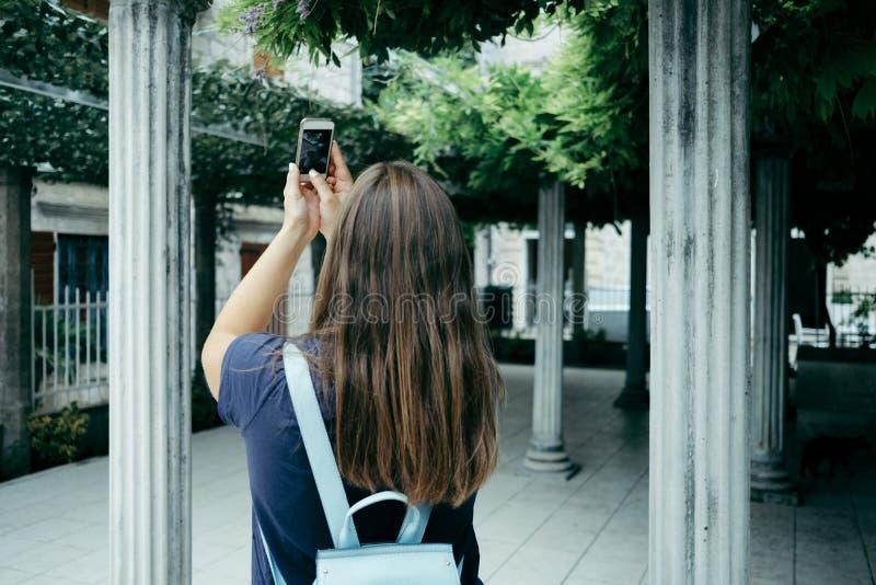 Opinião traseira o viajante da jovem mulher em um t-shirt azul com um backp fotos de stock