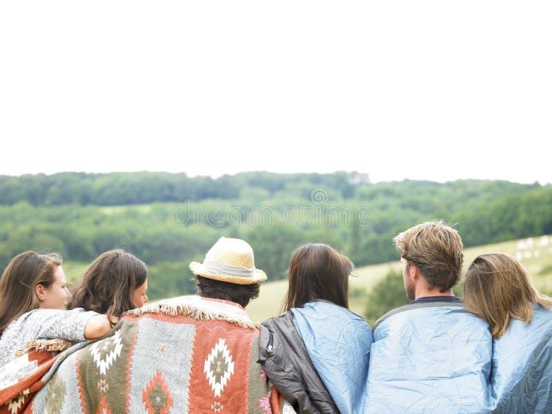 Opinião traseira os amigos ao ar livre com cobertores foto de stock royalty free
