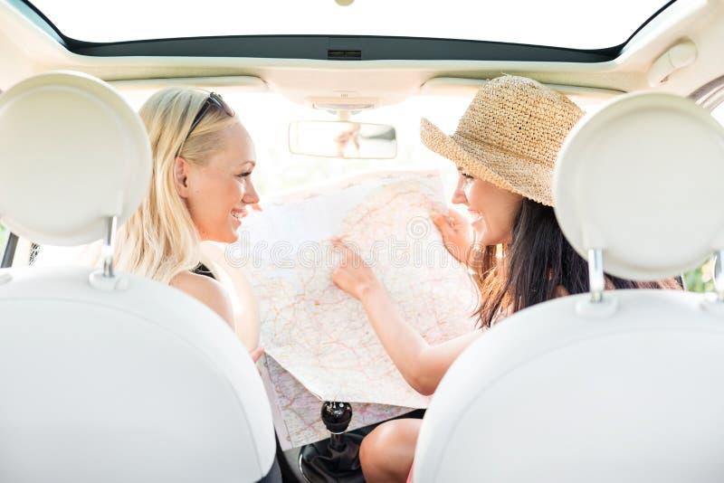 Opinião traseira os amigos fêmeas felizes que leem o mapa no carro fotografia de stock