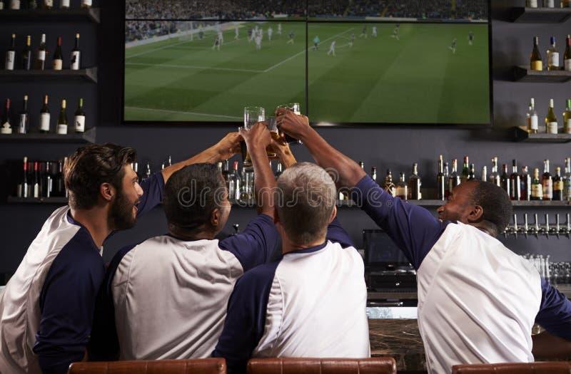Opinião traseira os amigos masculinos que olham o jogo na barra de esportes fotografia de stock royalty free