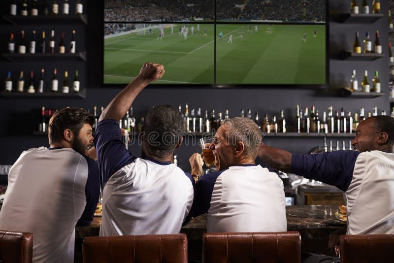 Opinião traseira os amigos masculinos que olham o jogo na barra de esportes imagens de stock