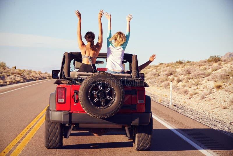 Opinião traseira os amigos na viagem por estrada que conduz no carro convertível imagens de stock royalty free