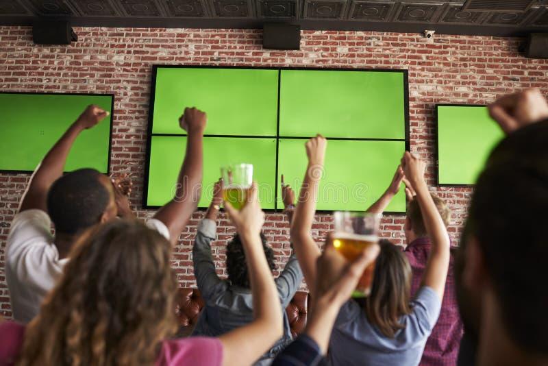 Opinião traseira os amigos que olham o jogo na barra de esportes em telas imagem de stock royalty free