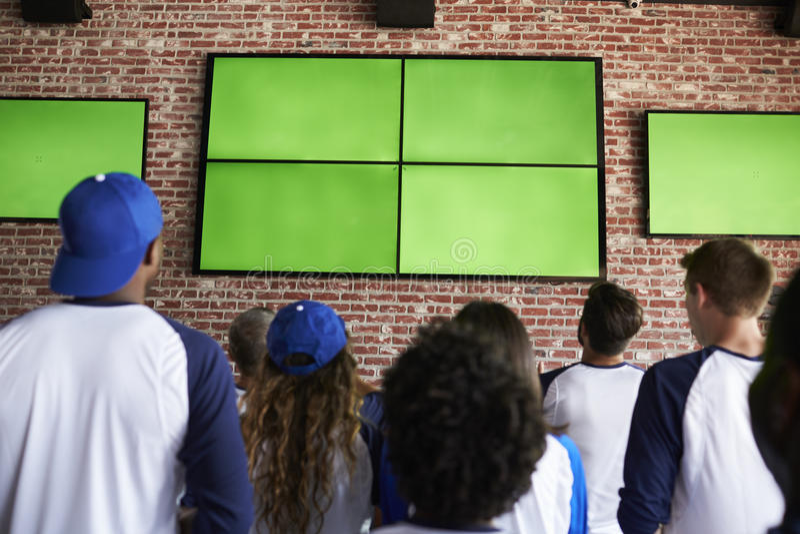 Opinião traseira os amigos que olham o jogo na barra de esportes em telas imagem de stock