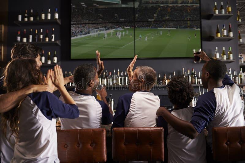 Opinião traseira os amigos que olham o jogo na comemoração da barra de esportes foto de stock
