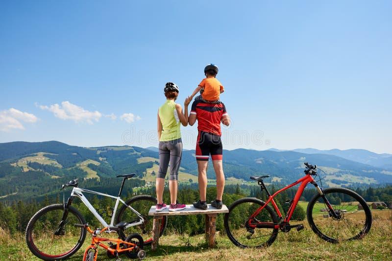 A opinião traseira os ciclistas desportivos da família que estão no banco de madeira, descansando após a ciclagem bicycles foto de stock