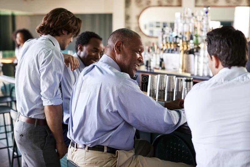 Opinião traseira os homens de negócios que encontram-se para após bebidas dos trabalhos na barra foto de stock royalty free